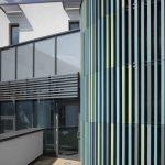 Vor den geschwungenen Glasfassaden sind knapp 120 cm lange keramische Rechteck-Rohre vertikal montiert. Diese filigranen Elemente verleihen dem Gebäude spielerische Rhythmik, schaffen reizvolle Ein- und Ausblicke bzw. interessante Transluzenz.