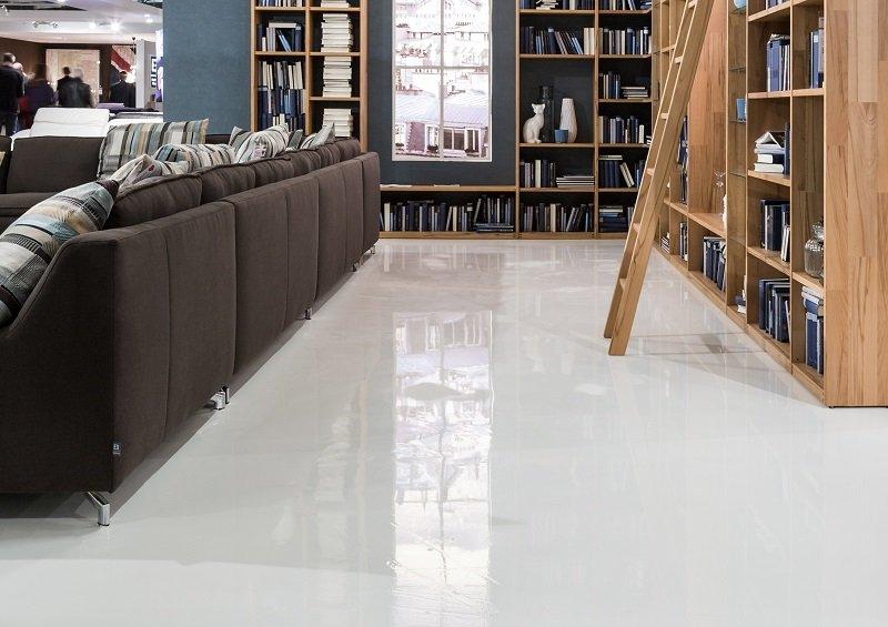 Im Wohnzimmer mit Bibliothek wurde die hochglänzende UV-beständige weiße Ver-laufsbeschichtung Arturo PU2030 verlegt. Der Boden mutet dabei wie eine edle Glas-fläche an.