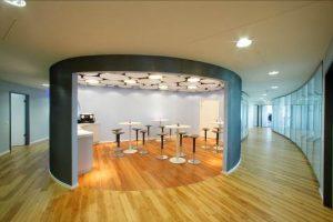 Der Coffee-Shop ist der zentrale Treffpunkt. In die runden Wandkörper sind großflächige Wandöffnungen und Türen eingearbeitet.