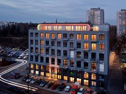 In der 1910 erbaute ehemaligen Textilfabrik entstanden nach dem Konzept e-wohnen auf vom ersten bis zum fünften Obergeschoss 32 barrierefreie Wohnungen mit fließenden Raumzonen. Die Penthouse-Etage ist als konvexer Dachkörper in Holzbauweise neu auf das G