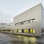 Eine klare, zeitlose und funktionale Architektur prägt den Neubau. Durch die Anlehnung der Fassadengestaltung an das Corporate Design des Unternehmens fügt sich dieser in das Gesamtbild des Werkgeländes ein.
