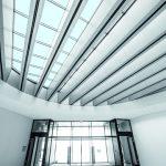 Die verglaste Atriumsdecke lässt viel Tageslicht ins Foyer.