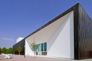 Der Quader bildet zusammen mit einem Riegel den neuen Multimediakomplex. Der helle Gebäudeeinschnitt in der dunklen Keramikfassade akzentuiert den Eingangsbereich mit dem dahinter liegenden Foyer.