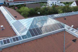 Tageslicht und Photovoltaik kombiniert: LAMILUX hat in die passivhaustaugliche Glasdachkonstruktion LAMILUX CI-System Glasarchitektur PR60energysave semi-transparente Dünnschichtmodule integriert.