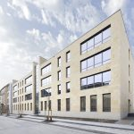Durch die Verwendung von hochwertigem Naturstein harmoniert die Fassade des Neubaus mit dem bestehenden Gerichtsgebäude.