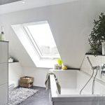 Die großzügige Dachfensterlösung lässt dank viel Tageslicht und einem freien Blick nach draußen das Bad optisch größer wirken.