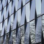 Als markantes Merkmal ist die Fassade aus gegeneinander geneigten, blau schimmernden Photovoltaik- und Glasmodulen weithin sichtbar.