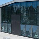Die umliegenden Gebäude spiegeln sich in der dreidimensionalen Glasfassade. Dadurch entstehen interessante Blickbezüge.