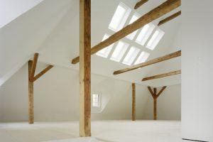 Die sichtbaren konstruktiven Hölzer verleihen dem Raum Struktur und unterstützen seinen ursprünglichen Charakter als Dachboden. Über die alte zweiläufige Treppe wurde der Dachraum erschlossen.