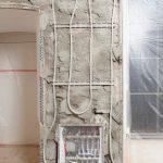 Auf schmalen Wandpfeilern wurden die Heizregister auch senkrecht verlegt. Hier mit einem der Verteilerkästen, für die vorhandenen Wandnischen ausgenutzt oder neue in das Mauerwerk gestemmt wurden.