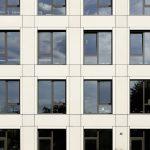 Durch eine im Beton ausgebildete, dreiseitig umlaufende Fasche und die Laibungsprofile der Fenster erfährt die Fassade eine zusätzliche feine Gliederung.
