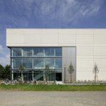 Großformatige, hell gefärbte Betonfertigteilplatten, pulverbeschichtetes Aluminium und Glas bestimmen die äußere Erscheinung.
