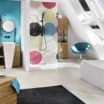 Farbkontraste und die Design-Dots der Duschwand sind wahre Eyecatcher in diesem Dachgeschoss-Bad und werden zusätzlich von den Spiegeln über dem Waschtisch aus Porzellan und Echtholz aufgenommen. Ins rechte Licht gesetzt werden die fröhlichen Punkte von s