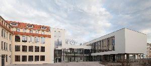 Die Neue Mitte Ichtershausen auf dem Gelände der ehemaligen Nadelfabrik: Links das denkmalgerecht sanierte Produktionsgebäude D, rechts daran anschließend der auf Stützen ruhende Mehrzwecksaal.
