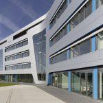 Großformatige, gebogene Glasflächen und silbergraue Alucobondplatten wechseln sich mit vertikal eingelegten blauen Lisenen, Bändern und Unteransichten im Sonderfarbton RAL 5015 ab, die die Firmenfarbe der FAM aufnehmen