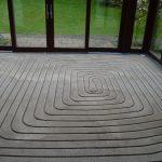 Der neue Estrich im Wintergarten ist gefräst und nun aufnahmebereit für das EMPUR Fußbodenheizungssystem CUT-THERM.