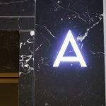 Mit dezent hinterleuchteter integrierter Anzeige ergänzt die BlendStone® Einrahmung in Nero Marquina die massive Naturstein-Einfassung des Aufzugsportals zu einem harmonischen Ganzen.