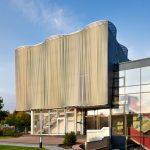 Innovative Textilfassade kombiniert mit farbiger Fassadenmembran Stamisol Color Geissblatt