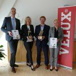 """Guido Schmidt, Leitung Key Account Management ibau (links) und Anja Gössel, Key Account Managerin ibau (rechts) überreichten am 28. Juni 2017 Silke Stehr und Stefan Beeg die zwei """"Stein im Brett"""" Awards für die Velux Deutschland GmbH."""