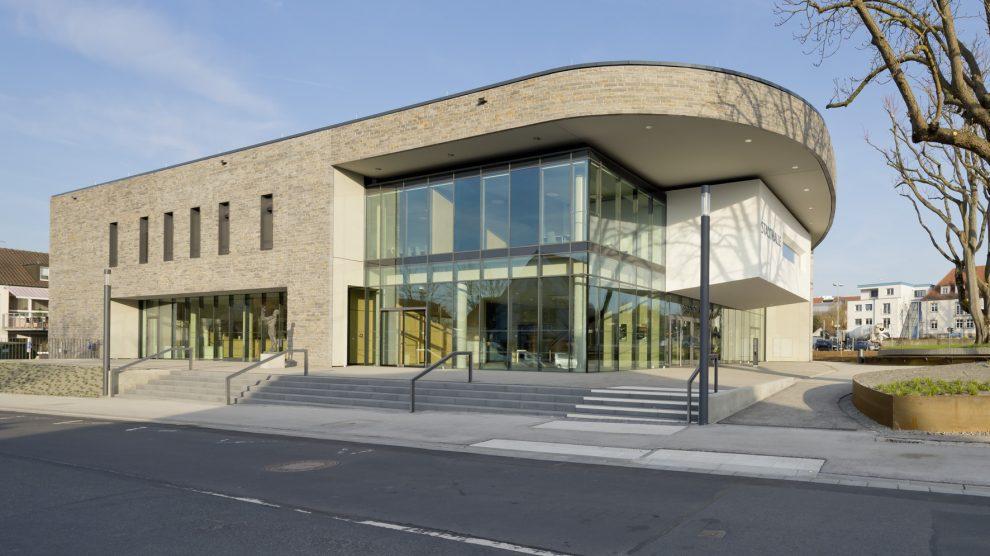 Im Norden und Osten öffnet sich die Stadthalle über eine transparente Pfosten-Riegel-Glasfassade der Umgebung.