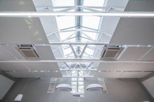 Die fertig montierten Deckensegel behindern nicht den Tageslichteinfall durch das Oberlicht und erhalten die großzügige Raumwirkung mit freiem Blick in die Dachbinder.