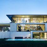 """OUTOFBOX Architekten beschreiben es als """"asketisches Design"""", tatsächlich erscheint das Objekt als eindrucksvolles Gebäude aus Glas und Sichtbeton, das sich organisch in das terrassierte Gelände integriert."""