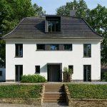 Straßenansicht nach dem Umbau: Symmetrisch angeordnete Fenster- und Türflächen strukturieren Fassade und Dach. Ein wiederkehrendes Element sind die schmalen, hochformatigen Stulpfenster (Schüco AWS 75.SI).