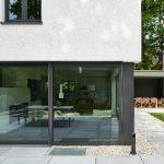 Betonplatten und Rheinlandkies markieren die Übergangszone zwischen Garten und Haus. Die dunklen Rahmenprofile der Lichtöffnungen bilden strukturierte Kontraste zu den hellen Flächen.