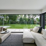 Das fast 13 m² große, ungeteilte Festfeld hebt die Trennung zwischen Wohnraum und Garten optisch nahezu vollständig auf (Schüco AWS 75.SI).