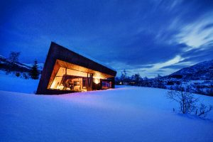 """Großflächig verglaste, schmal profilierte Fassadenbereiche sind kombiniert mit rostrotem Cortenstahl und Fichtenpaneelen: das Wohnhaus """"Black Lodge"""" in Ålesund, Norwegen."""