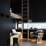 Hell-dunkel-Kontraste durch Lichteinfall, Materialien und Farben: Schmale vertikal und horizontal arrangierte Fensterbänder durchschneiden die schwarz lackierte Holzverschalung der Wand- und Deckenflächen.