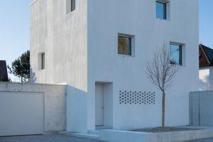 Haus D in Mering. Mit seiner klaren, fast turmartigen Form hebt sich der Putzbau von seiner Umgebungsbebauung ab.