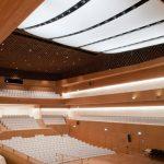 Die hochkomplexe Konstruktion des Deckensegels sorgt für perfekten Klang auf allen Plätzen im Saal. In den Zwischenräumen der einzelnen Elemente ist die Bühnenbeleuchtung integriert.