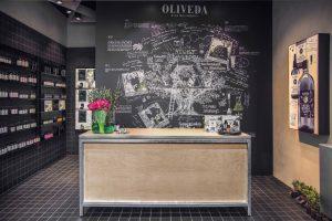 Der Oliveda Flagship Store in Düsseldorf nimmt Bezug auf die Kernelemente der Markengeschichte wie beispielsweise das Baumhaus, in dem 2001 das erste Elixier entstand. Die Produktpräsentation ist zudem von einer apothekenartigen Laborumgebung inspiriert.