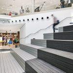 Gleich an das Wasserbecken schließen die Sitztribünen für Zuschauer. Die Zugänge erschließen sich über Treppen, die man vom Erdgeschoss aus kommend erreicht. Diese Steilanlage hat eine Unterkonstruktion in Holzständerbauweise, auf der die Dielen mit unsic